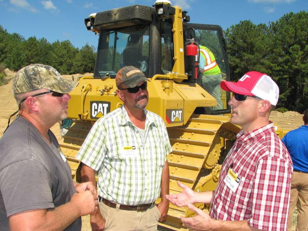 (L-R): Jeff Flake and Cory Mason, both of Elm Services, Helena, Ala., and Grady Burchfield, Thompson Tractor, discuss their experience with grade control machines.