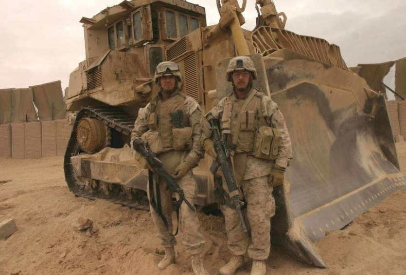 Photo courtesy of U.S. Marine Corps Sgt. Josh Hauser. Chief Warrant Officer 4 Alan J. Clyne, left and Master Sgt Scott E. Witmer stand in front of the Caterpillar D9 dozer they used to clear a path to safety to stranded Marines during Operation Steel Curtain.