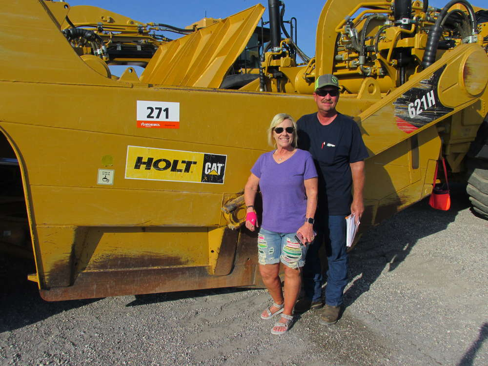 Brenda (L) and Jeff Wetzel of Big Iron Heavy Equipment Construction in Blanket, Texas, are very interested in this Cat 621H scraper.