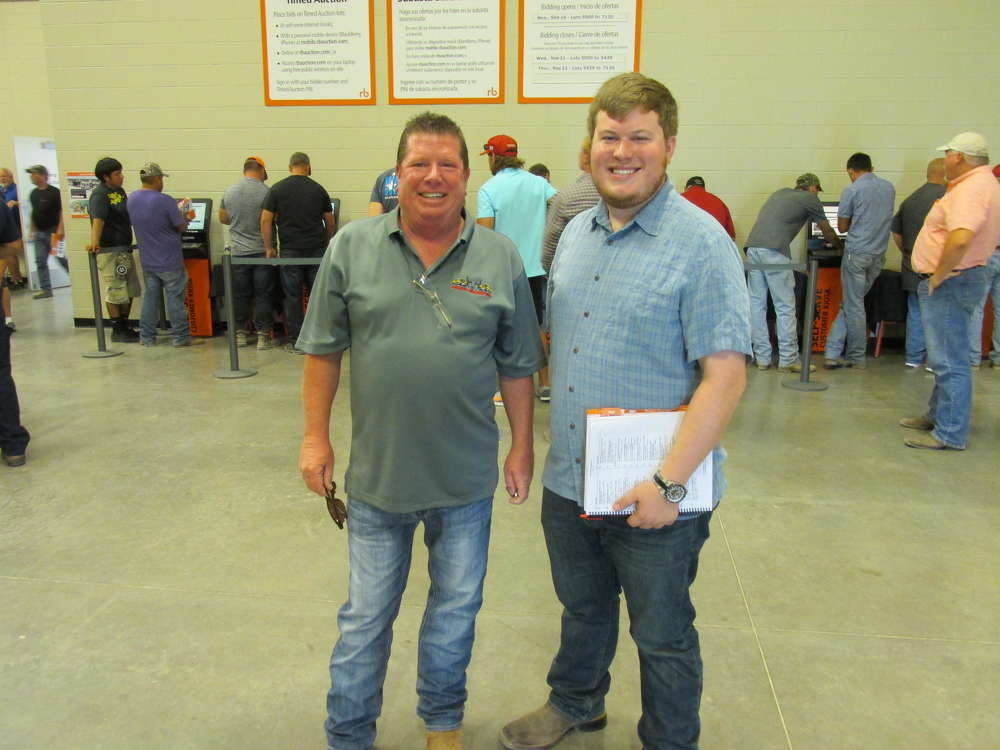 Jeff Miller (L) and his son, Maxx, of Trophy Tractor in Grand Prairie, Texas, take a quick break after a hard day of bidding.