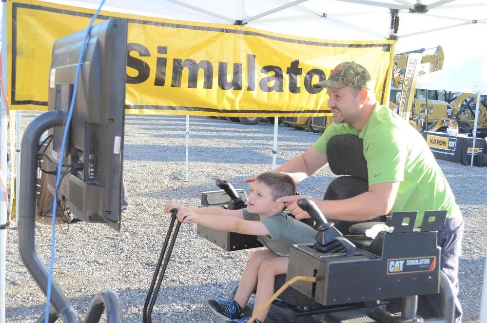John Gosevski, H.O. Penn, coaches his son, Benjamin, on a simulator.
