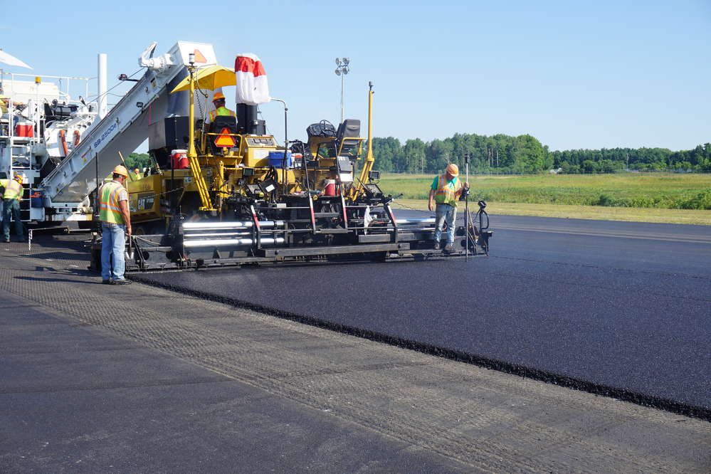 A Suit-Kote screed operator checks the finish grade mat elevation with a grade check rover rod.