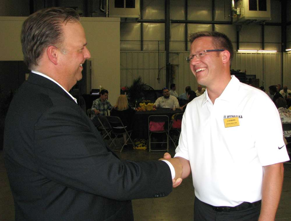 Jon Cruthers (L), vice president of sales of AED, Schaumburg, Ill., receives a warm welcome from Kris Binder, Hydrema.