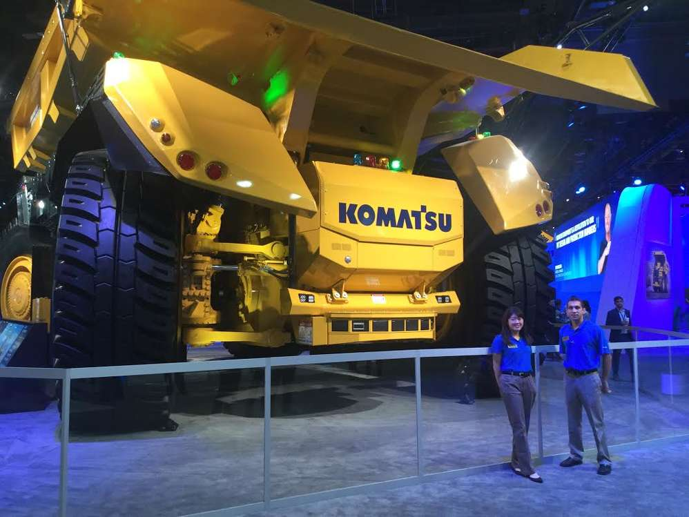 Sayuri Tsuji (L) and Jonathan Tolomeo, product managers of Komatsu, display Komatsu's latest 930E electric drive truck.
