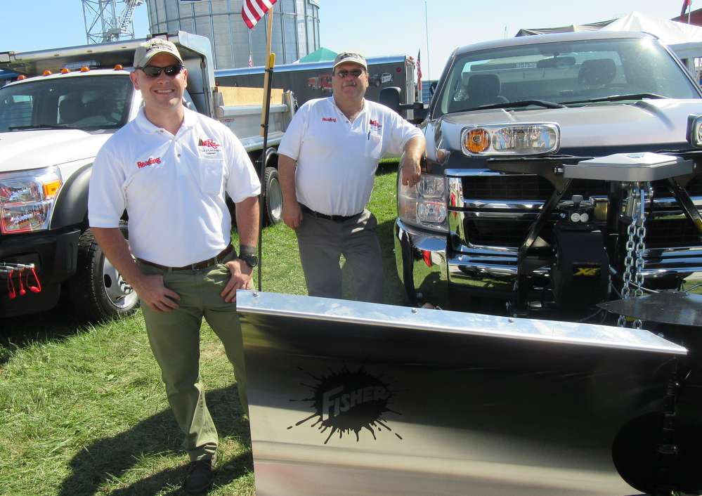 Cory Walters (L) and Erich Rose, both of KE Rose Company, stand with this Fisher Engineering snowplow.