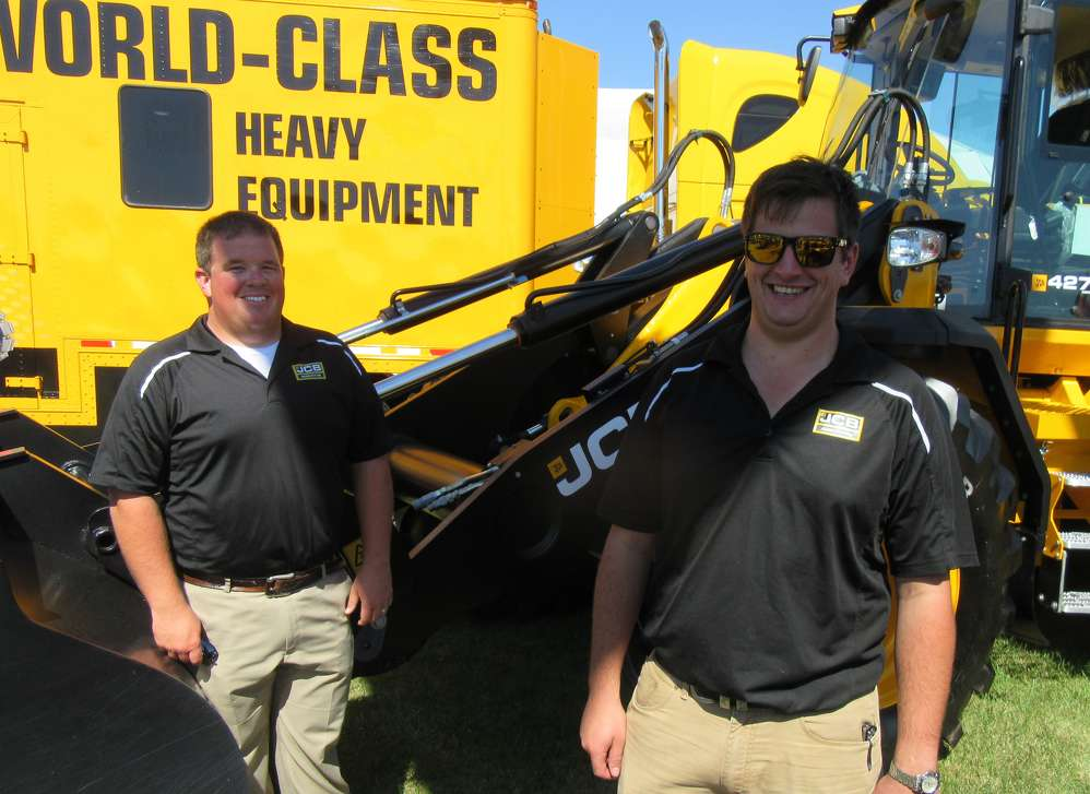 Brandon Hawkins (L) and Bruce Mustard of JCB  show attendees equipment, including this JCB 427 agri wheel loader.