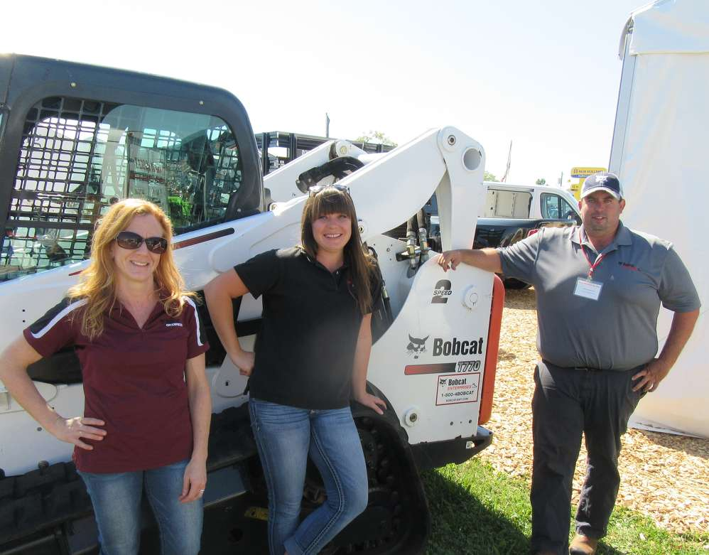 (L-R): Heather Murray, Meghan Fellure and Lenny Garrard, all of Bobcat Enterprises,  wait to answer questions about used Bobcat equipment.