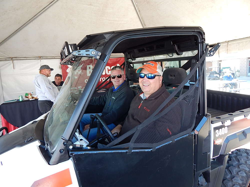 Chad Shea (L), rental manager, Swanston Equipment, Fargo, N.D., sits with Chad Tatum, salesman of the year, in a Bobcat 3400.