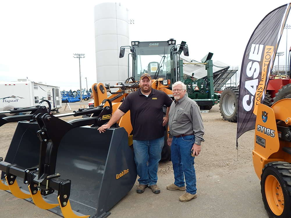 Travis Lindekugel (L), sales manager of GrabTech Manufacturing, Larchwood, Iowa, stands with Harold Watnemo, Titan Machinery field marketer, Fargo, N.D., and a Case 521FXR wheel loader.