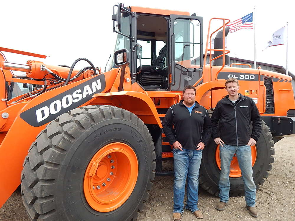 Chris Landis (L), sales specialist, Ironhide Equipment, Grand Forks, N.D., and Nathan Cain, Doosan Infracore product trainer, Fargo, N.D., stand with a Doosan DL300 loader.