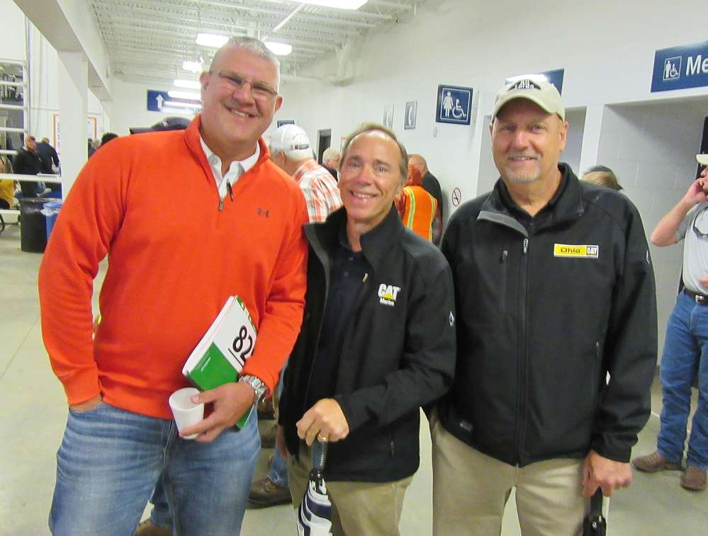 (L-R): Jon St. Julian of Columbus Equipment Company talks with Eric Emch and Bill Kuhar, both of Ohio CAT, at the auction.