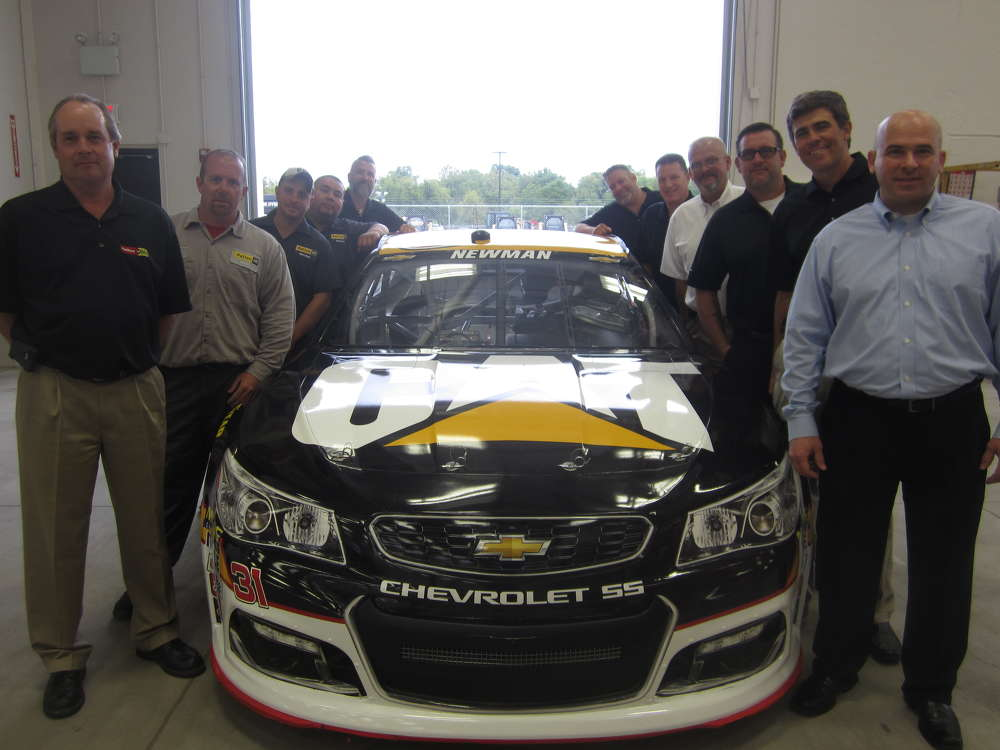 Frank Bart, Wauconda, Ill., mayor (front right) and Garrett Patten, president of Patten CAT (second on the right) stand with the employees of Patten CAT around the Cat race car driven by Ryan Newman.