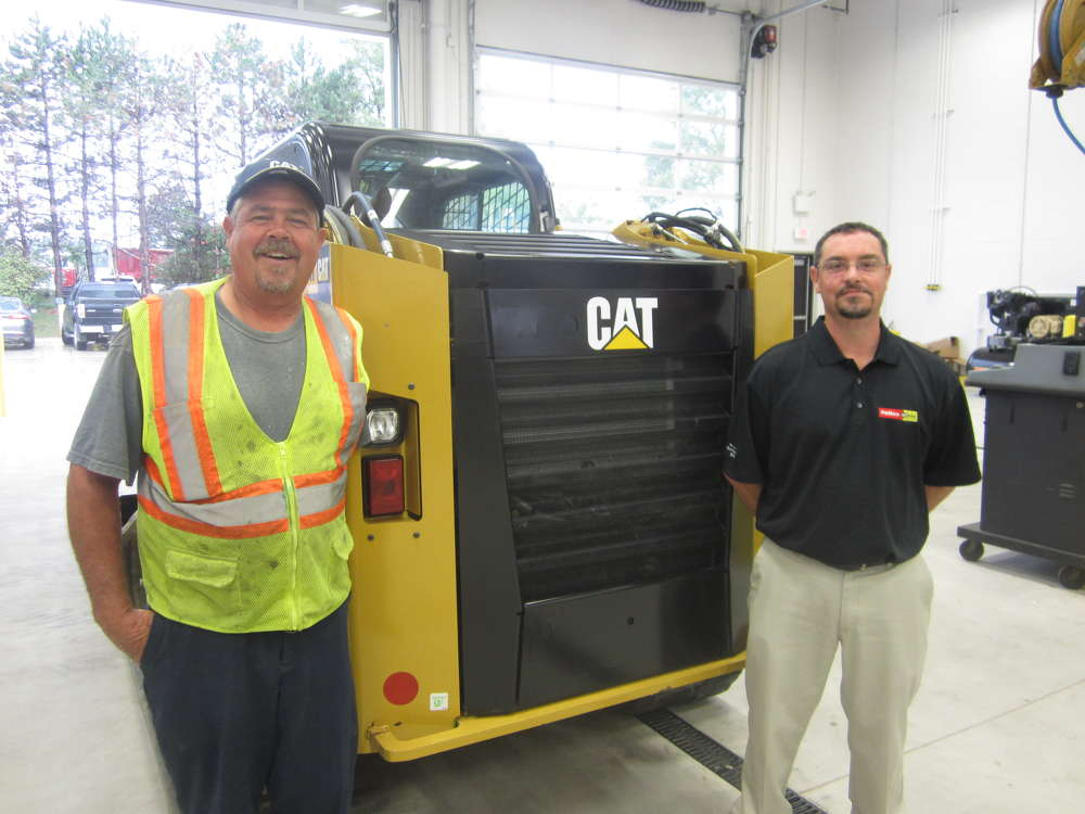 Kevin Zupec (L), Campanella & Sons Inc., and Joe Mistretta, Patten CAT sales representative, stand next to the Cat 279D track skid steer.