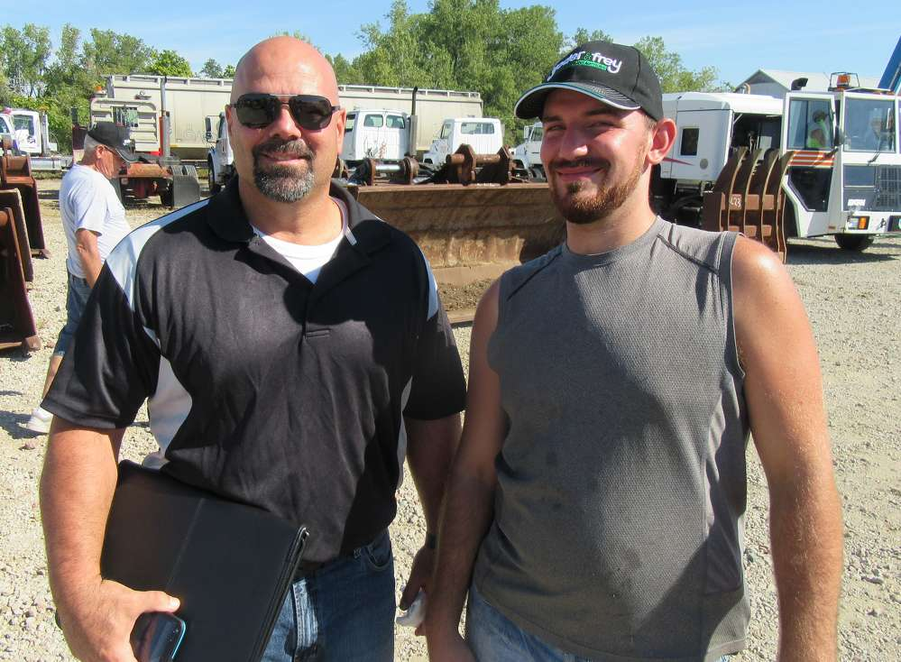 Chris Fanzini (L) of Allen Holdings, owner of the auction site, speaks with Adrian Keiper of Keiper Excavating in Wadsworth, Ohio, who purchased a Caterpillar 262 skid steer at the auction.