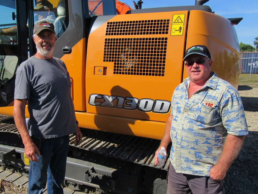 Dave Horst (L) and Marvin Edwards of Crooked Oak Farms consider bidding on this Case CX130D excavator.