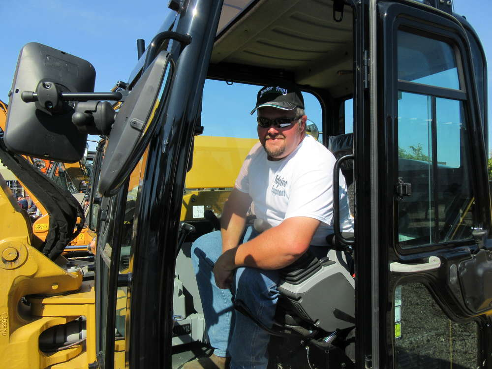 Rick Hooser of Ridgeline Equipment who came in from Barboursville, W. Va., checks out this Caterpillar 308 excavator at the auction.