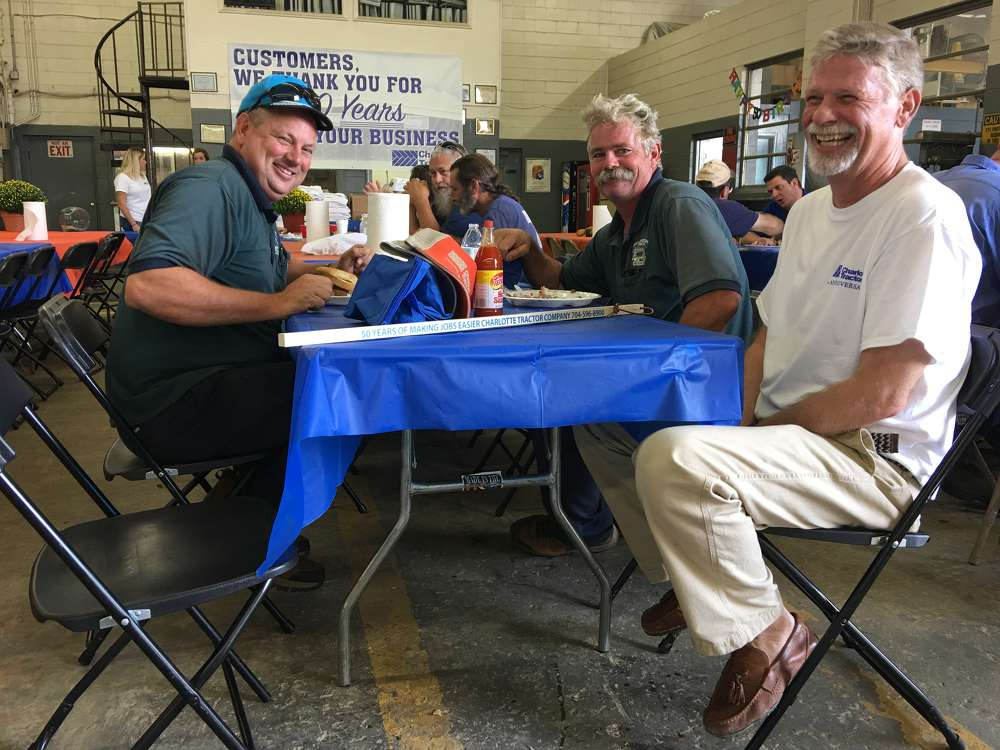 Tim Cockerham (R) of Charlotte Tractor Company welcomes David Martin (L) and Doug Cook, both with Martin Landscaping Company in Charlotte.