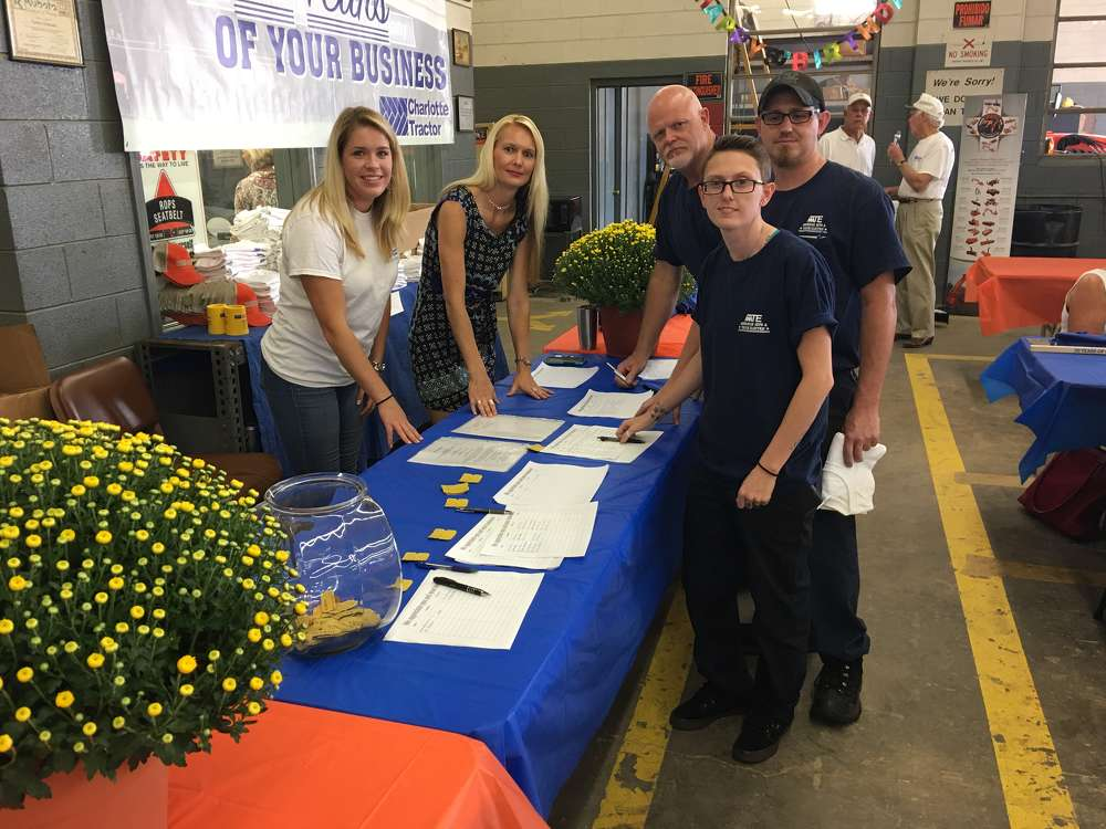 Nicole Cockerham and April Robinson,  both of Charlotte Tractor, welcome Boyd, Ashley and Joshua Honeycutt, all of American Auto & Truck Electric in Charlotte, to the celebration.