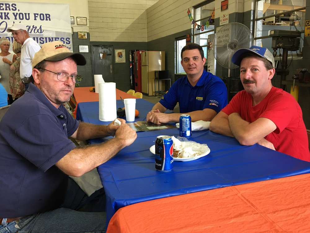 William Mason (L) and David Furr (R), both of Charlotte Pipe & Foundry, talk with Ben Demanee of New Holland.