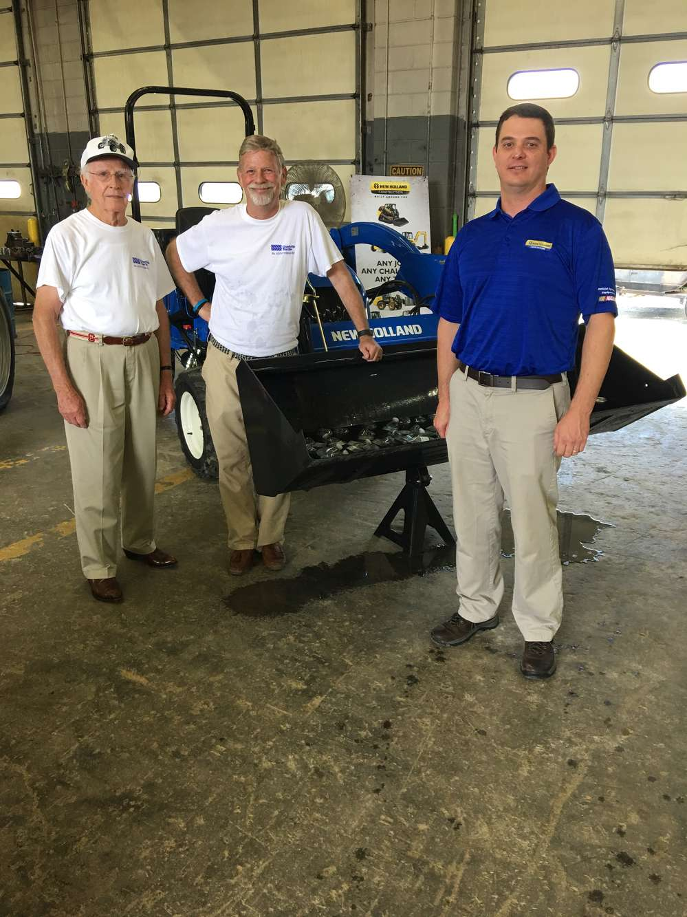 (L-R): Bob and Tim Cockerham of Charlotte Tractor talk with Ben Demanee, New Holland Territory business manager.