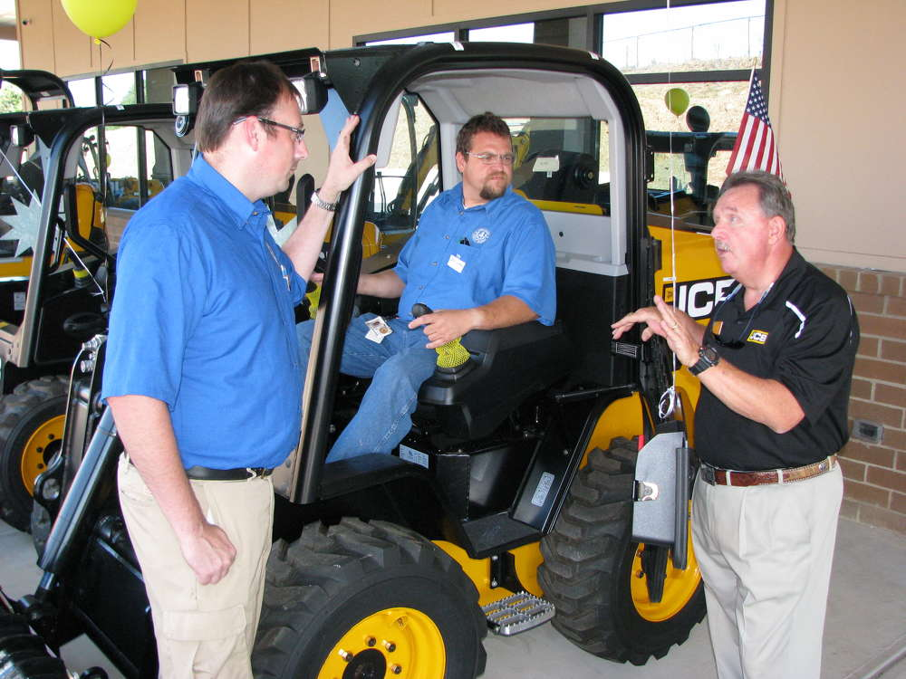 Larry Ashley (R) of JCB points out the safety features of the JCB 260 skid steer loader to Mark Reida (L) and Dana Goodman, staffers of Cobb County, Ga.
