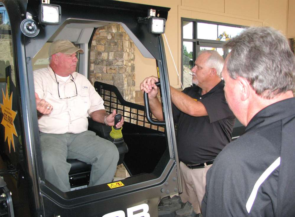 (L-R): Ed Bentley of Bentley Investment Management, Marietta, Ga., asks Lee Barnes, Atlanta JCB, and Larry Ashley, JCB, questions about the machines.