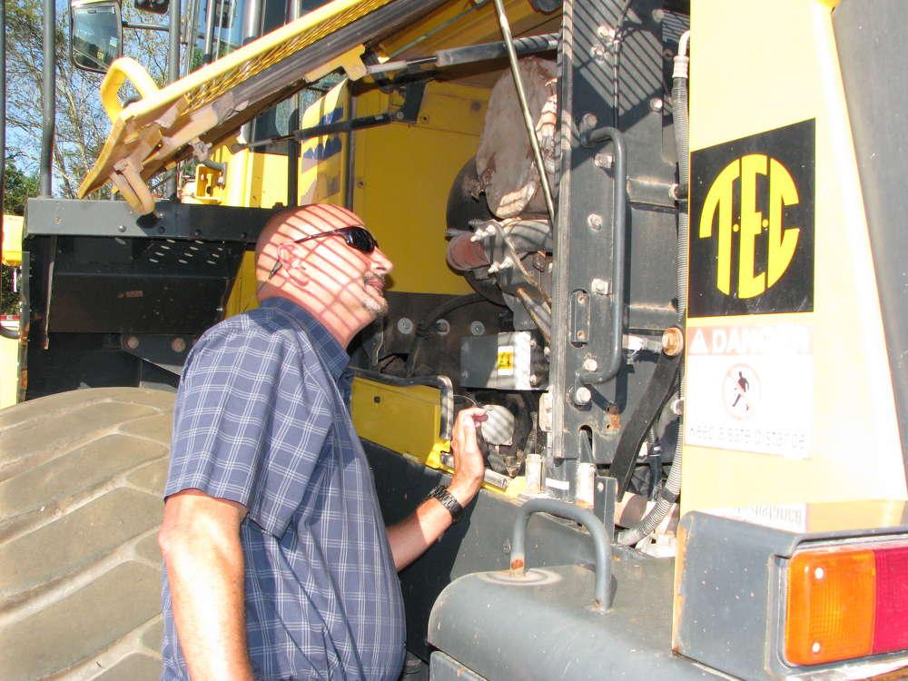 Tim Thomas of Tractor & Equipment Co., Birmingham, Ala., looks at the engine of a Komatsu WA380 wheel loader.