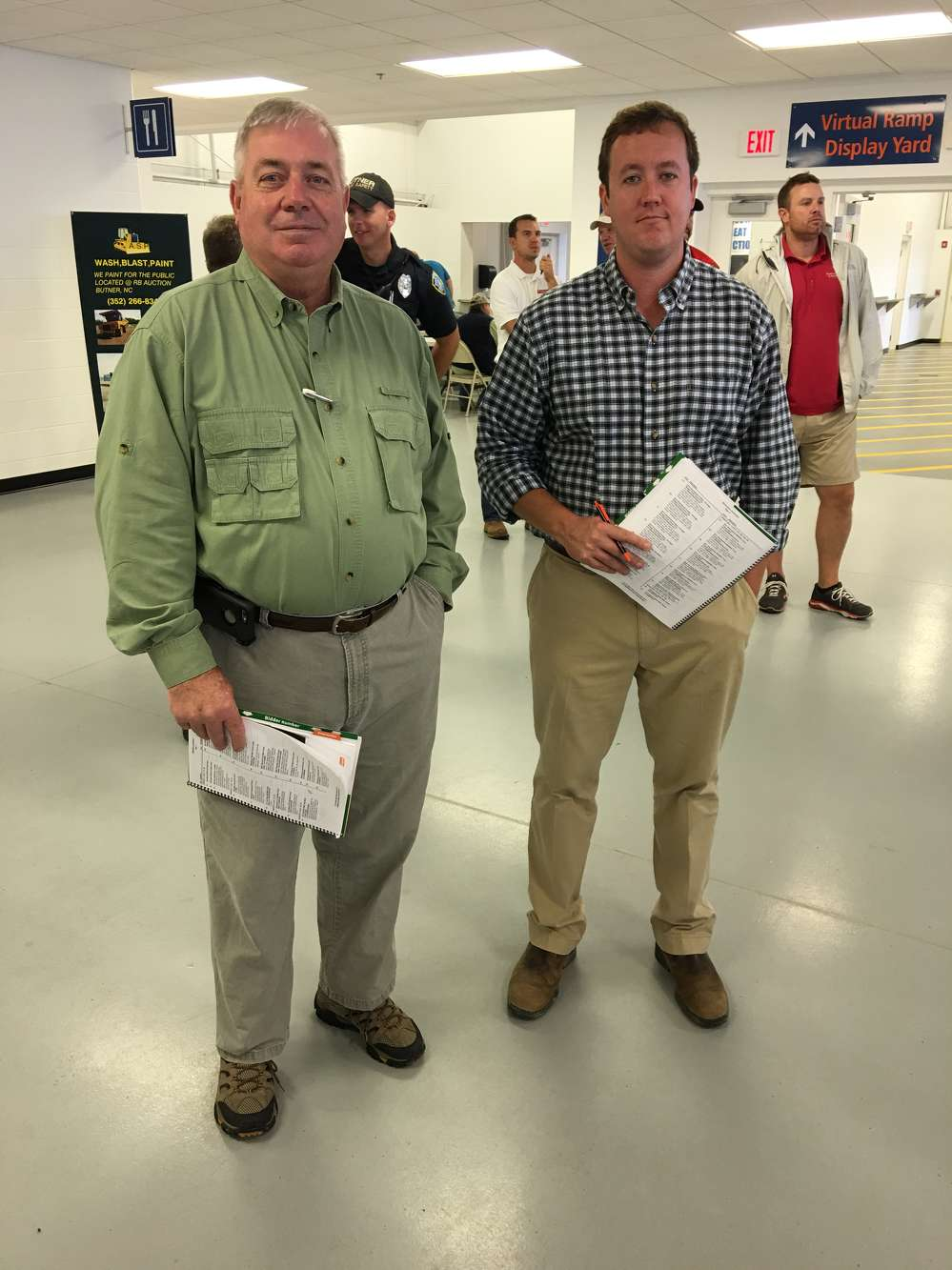 Wayne Calton (L), Gregory Poole Equipment Company, and Tim Eldridge, Carter Machinery, follow the bidding.