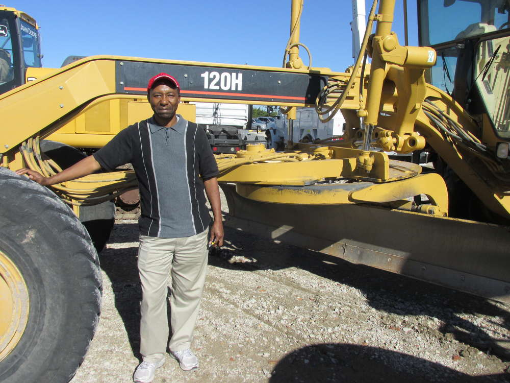David Omete of MZEE's Property Inc. in Flower Mound, Texas, hopes to have the winning bid on this 120H Cat motorgrader.