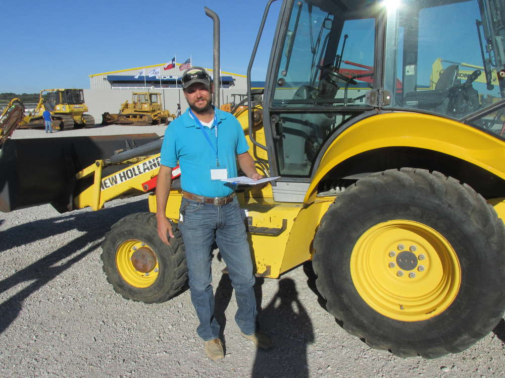 """Tike Davis of Big County Stone in Abilene, Texas, has given this New Holland B95 backhoe a thorough """"once over"""" before bidding."""