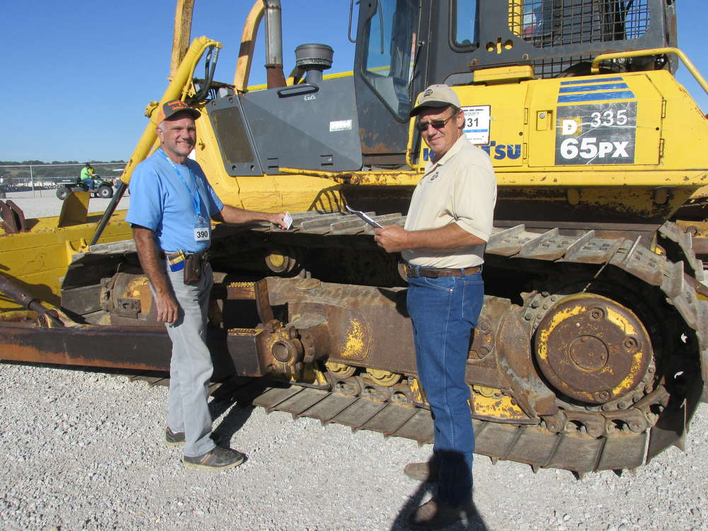 David Hughes (L) and Bubba Stone, independent contractors from Groesbeck, Texas, feel they just have to have this Komatsu 65 dozer.