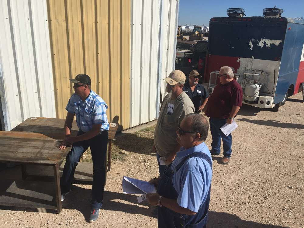 Customers patiently wait for the backhoes to be auctioned off in Stanton, Texas.