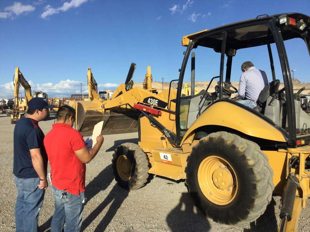 (L-R): Paulo Gonzales, Everardo Samaniego and Geraldo Ritchie, all contractors from Southern California, test this Cat 430E backhoe.