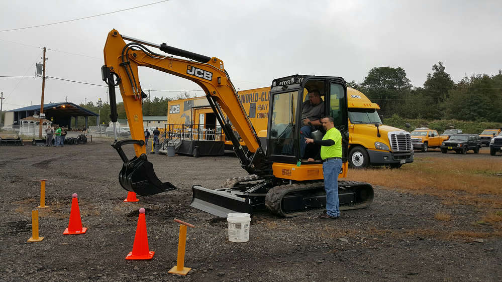 SEI's Wilkes-Barre, Pa., branch manager Dave Donati (R) goes over the JCB operator skills challenge with Alex Ramer of Penn Township before he starts. The JCB event truck seen in the background was on hand for the event.