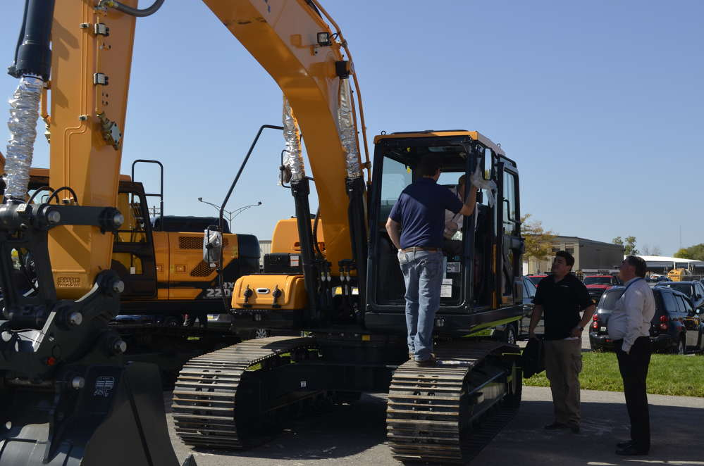 Interested buyers seek information on the Hyundai excavators from factory representatives.