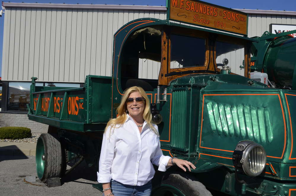 Tracy Saunders, president of W.F. Saunders, stands proudly with her 1925 Mack truck that has remained in the W.F. Saunders fleet all these years.