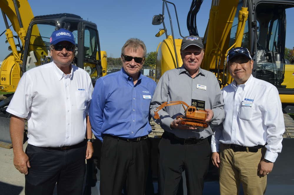 Kobelco presents Jerry Tracey with a hand-crafted wooden model of a Kobelco excavator to commemorate Tracey Road Equipment's 40th anniversary and long history with Kobelco. (L-R): Terry Ober of Kobelco; Randy Hall of Kobelco; Jerry Tracey of Tracey Road Equipment; and Pete Morita, president and CEO of Kobelco.