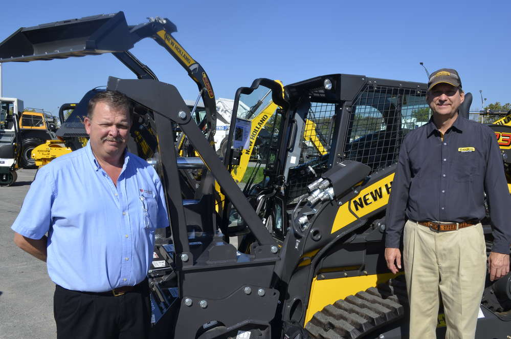 Andy Neff (L), factory representative of Paladin, and David Kohuth of New Holland demonstrate that this New Holland excavator can accept any one of dozens of specially engineered attachments manufactured by Paladin.