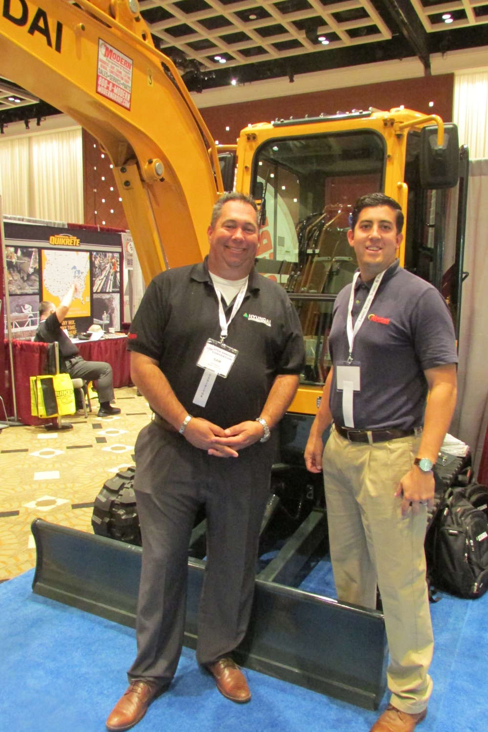 Proudly standing in front of a Hyundai excavator are Sam Maury (L), general manager of heavy construction equipment, and Ron Dortone Jr., sales representative, construction equipment division.