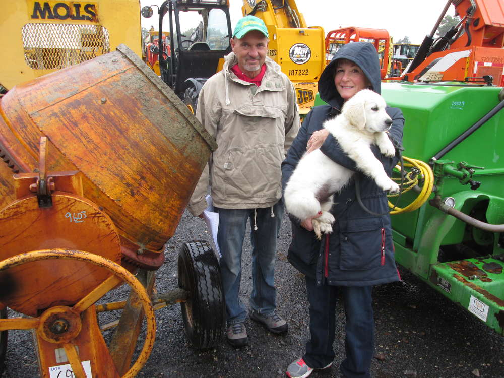 Gary and Bonnie Santoro, owners of Gary J. Santoro Mason Contractors of Bethlehem, Conn., with their 12-week-old retriever Bentley, look at various consignment equipment up for auction. Someone actually bid $1,000 on Bentley, but the pup was not for sale.