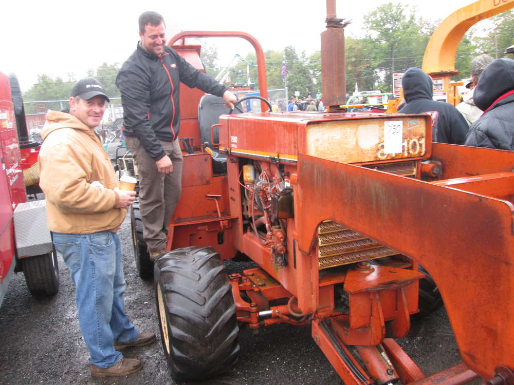 Brothers Joe (L) and Louis Vaz, owners of Vaz Quality Works of Bridgeport, Conn., inspect a Ditch Witch on the grounds.