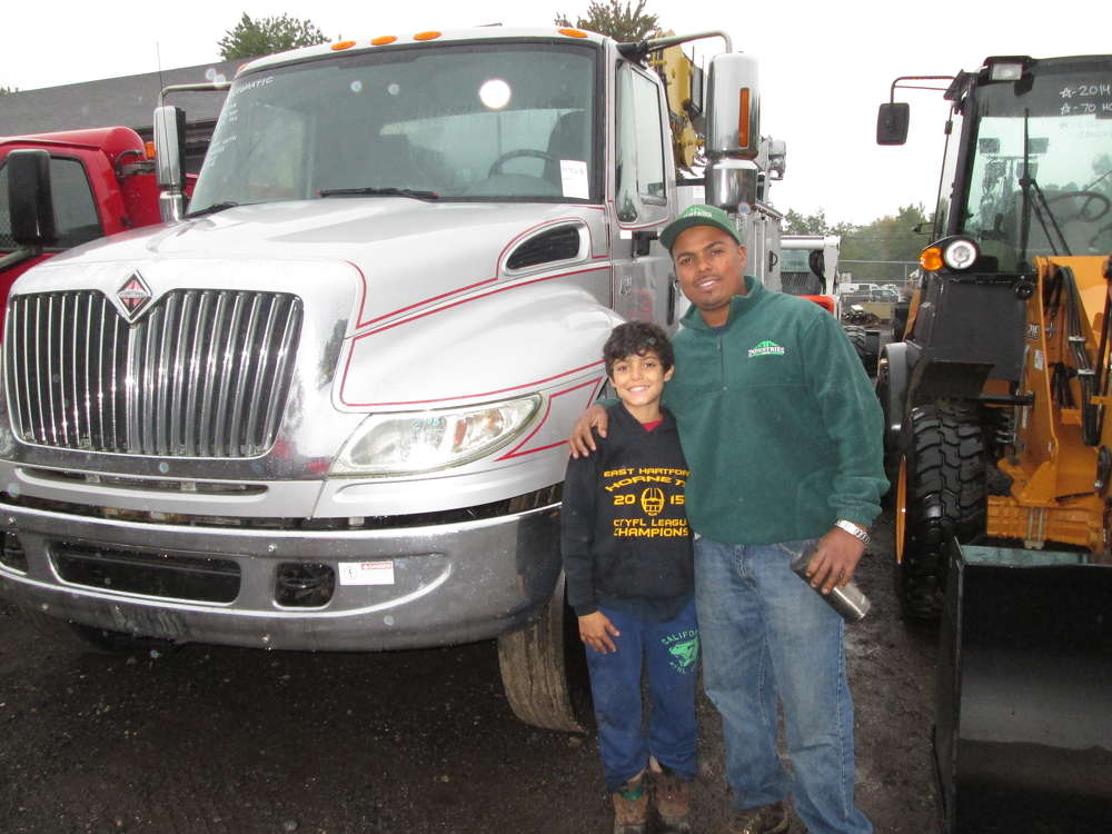 Alex Alvarez, owner of AA Industries of South Windsor, Conn., brought his son Anthony Alvarez to the auction. Alvarez was interested in the service truck behind them.
