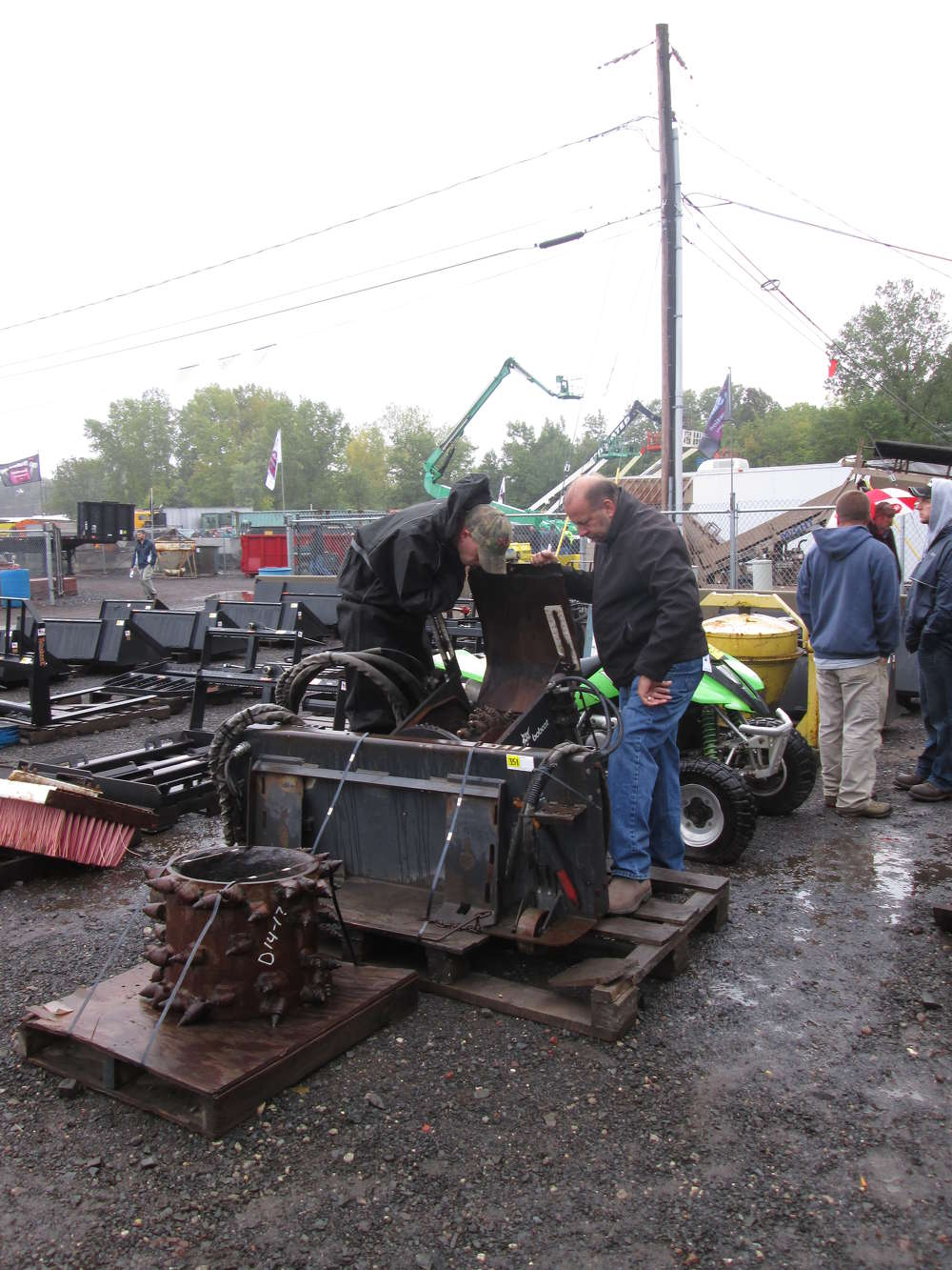 Erik Hansen Jr. (L) and Erik Hansen Sr. of Scavo Construction, Patterson, N.Y., carefully examine a piece of machinery.
