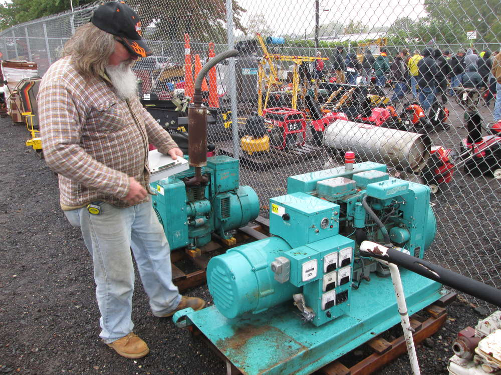 Charlie Emerson, owner of C.M.E. Excavation of Salbury, Mass., examines a 1600-watt generator he considered buying.