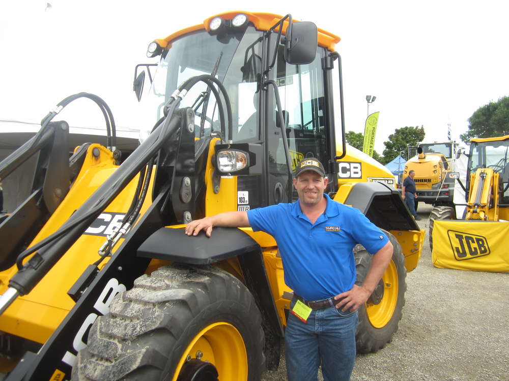 Jeremy Seavers mans the Fairchild Equipment Co. display area and stands in front of this JCB 411 HT wheel loader.