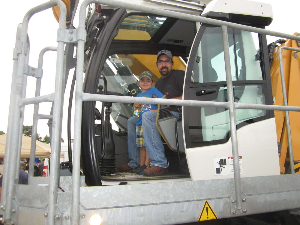 Jordan St. John of St. John Forestry Products shows his son, Jase, the controls of this Liebherr LH-50 material handler.
