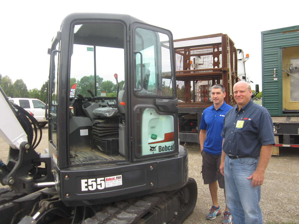 Jim Radart (L) and Paul Cappelle, both of Bobcat Plus, check out this Bobcat E55 mini-excavator.