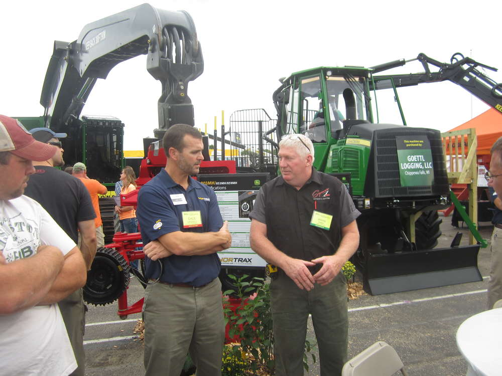 Dale Gessell (L), vice president of Nortrax, speaks with Brian Zabel of Zabel's Sawmill about John Deere forestry products.