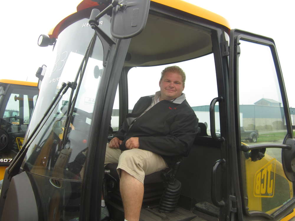 Andrew Mosier, Mosier Excavating, looks over the cab of this JCB 407 compact wheel loader.