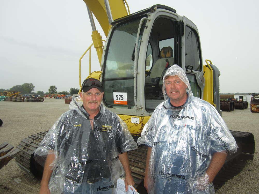 Craig Ferguson (L), owner of Ferguson Trailer Sales, and Jay Hawkinson, Ferguson Trailer Sales, look over the undercarriage of this Kobelco SK200 excavator.